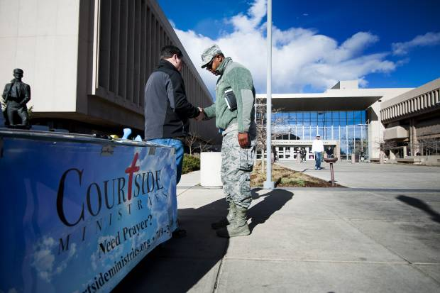 Courtside Ministries volunteer Quentin Valdois, left, offers a prayer for Corey Trusty as he leaves the El Paso County Terry R. Harris Judicial Complex